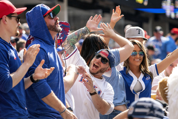 Image: Texas Rangers fan Anthony Sosa, center, celebrates with friends during the fourth inning of a baseball game against the Toronto Blue Jays, Monday, April 5, 2021, in Arlington, Texas.