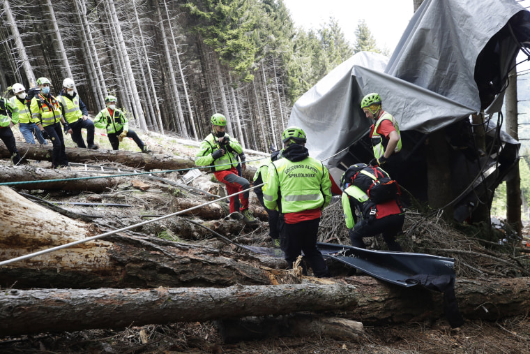 Rescuers search for evidence in the wreckage of a cable car after it collapsed near the summit of the Stresa-Mottarone line in the Piedmont region, northern Italy, on May 26, 2021.