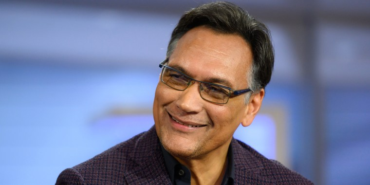 A middle aged man with salt and pepper hair wearing black glasses smiles at the camera