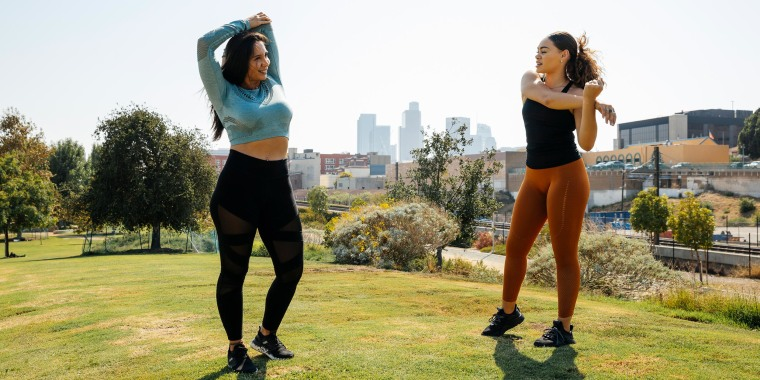 Female friends stretching before exercise at park