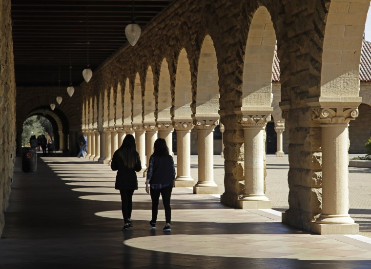 Image: Students walk on the Stanford University campus in Santa Clara, California, on March 14, 2019.