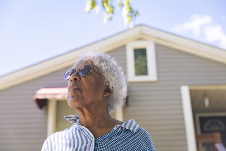 Priscilla Giles stands in front of her childhood home in Evanston, Ill.