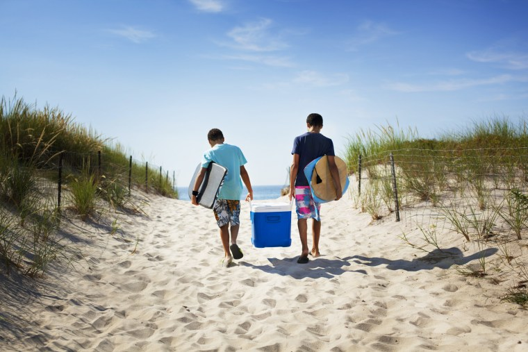 Two brothers carry a cooler on the beach. These are the best coolers to try in 2021. See cooler bags and soft coolers from YETI, RTIC, Igloo and more to keep your food and drinks cold this summer.