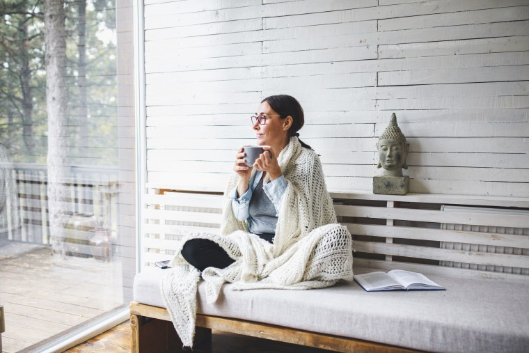 Woman sitting comfortable and looking through the window. See the best teas for your health. Learn about the health benefits of teas and shop matcha green tea, oolong tea and more to add to your daily routine.