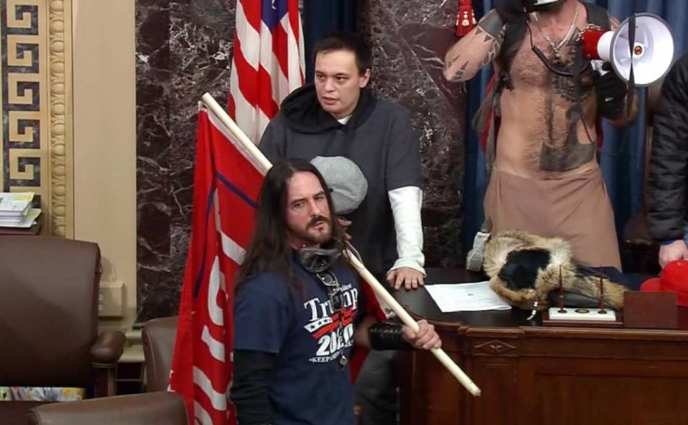 """Image: Paul Allard Hodgkins carries a large red \""""Trump 2020\"""" flag inside the Senate chamber during the Capitol riot on Jan. 6, 2020."""