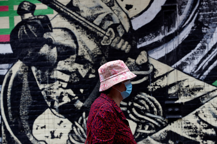 Image: A woman wearing a protective face mask walks by a mural following the May 31, 2021 unprovoked attack on a 55 year old Asian woman, in Manhattan's Chinatown district of New York City
