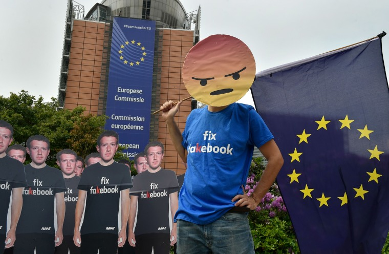 """Image: Global activists set up cardboard cutouts of Facebook chief Mark Zuckerberg, on which is written  \""""Fix Fakebook\"""", in front of the European Union headquarters in Brussels."""