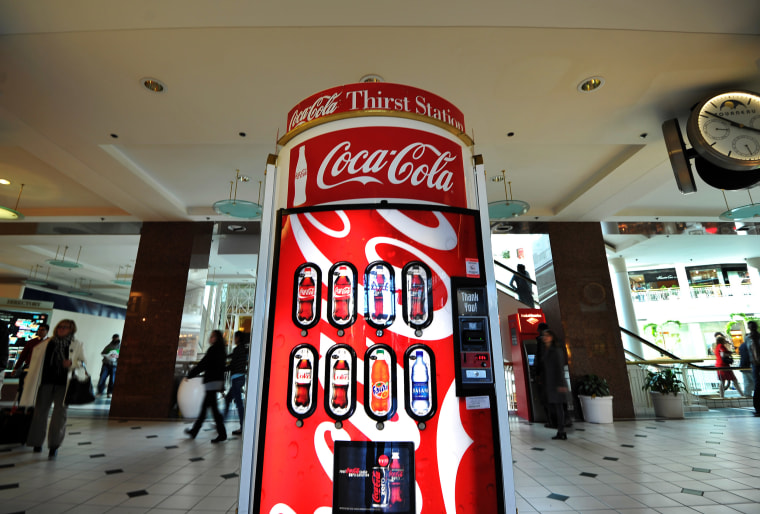Image: People walk past a Coca Cola vending machine at a shopping mall in Arlington, Va.