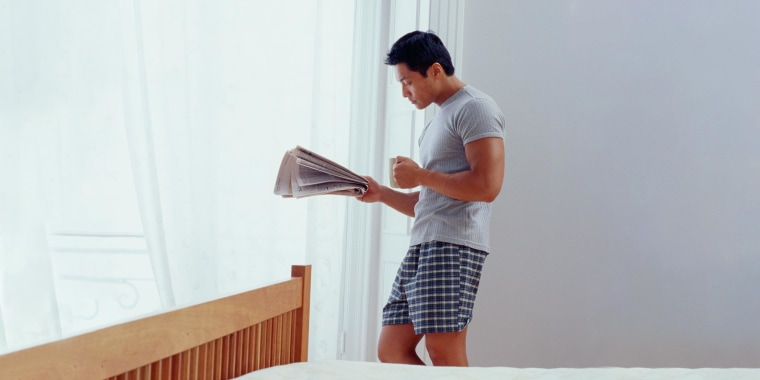 Man Reading Newspaper in Bedroom in his boxers