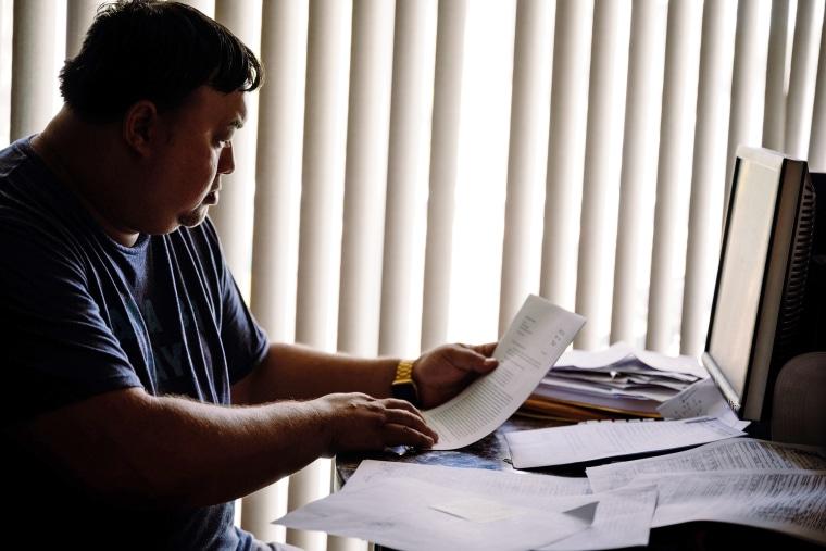 Image: Robert Jones looks over documents relating to his son's arrests.
