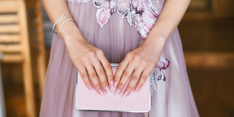 Woman hands holding a pink clutch