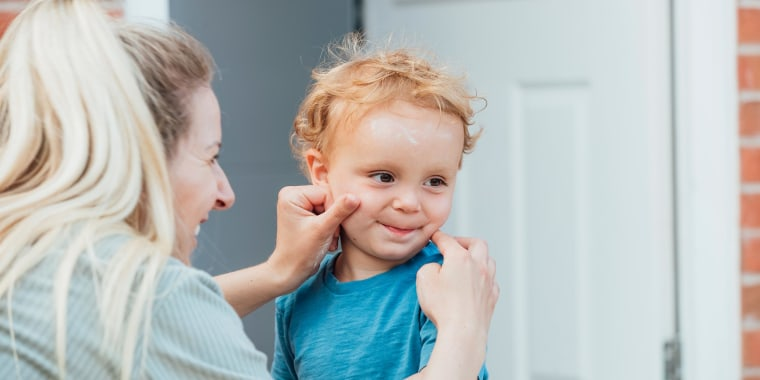 Woman putting sun cream on her son's face while he is looking away from her and the camera, outdoors in their home garden