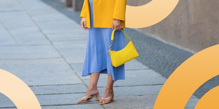 Woman wearing a yellow jacket and holding a yellow purse with tan sandals