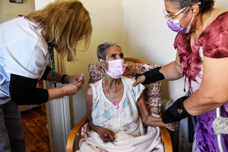 Idalia Vazquez, 83, receives her second dose of a Covid-19 vaccination from Helen Turchioe, left, who is part of a team of vaccinators administering shots to homebound seniors in Yonkers, N.Y., on March 29, 2021.