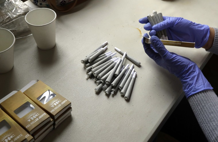 Image: A worker at the Hollingsworth Cannabis Company packages pre-rolled marijuana joints near Shelton, Wash.