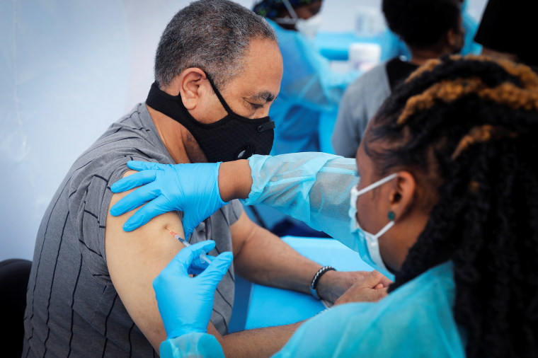 Image: 72-year-old Jay Hernandez receives a dose of the Pfizer-BioNTech vaccine during a vaccination event for local adolescents and adults outside the Bronx Writing Academy school in New York City