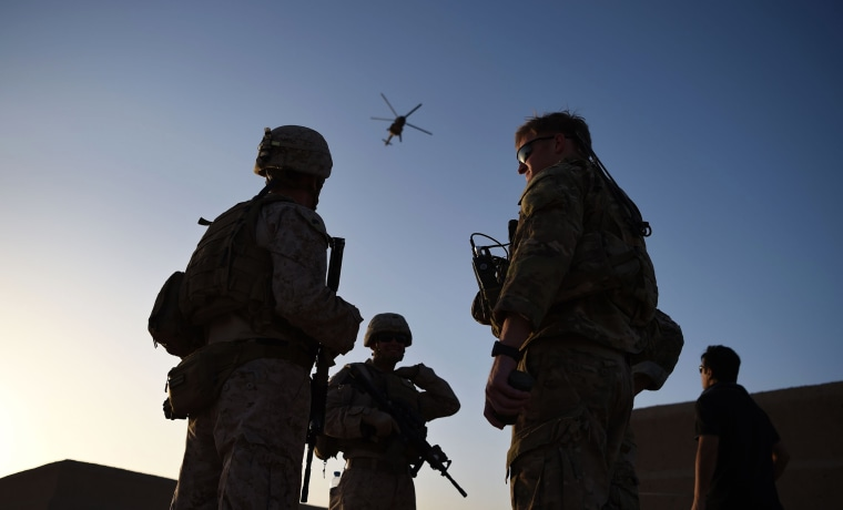 U.S. Marines and Afghan Commandos stand together as an Afghan Air Force helicopter flies past during a combat training exercise at Shorab Military Camp in Lashkar Gah in Helmand province, Afghanistan, on Aug. 27, 2017.