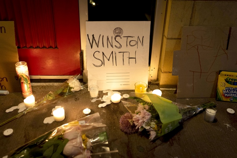 Image: Candles and flowers are arranged at a vigil for Winston Boogie Smith Jr. early on June 5, 2021.