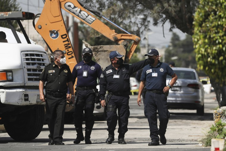 Police walk outside the house where bones were found under the floor in the Atizapan municipality in Mexico, on May 20, 2021.