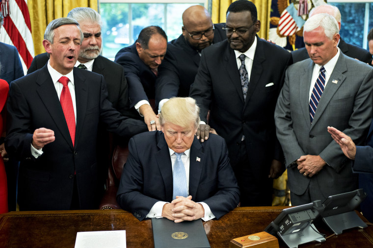 Then-President Donald Trump bows his head during a prayer while surrounded by then-Vice President Mike Pence, faith leaders and evangelical ministers after signing a proclamation declaring a day of prayer in the White House on Sept. 1, 2017.
