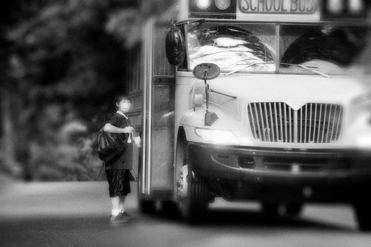 Image: School bus picking up elementary student wearing surgical mask.