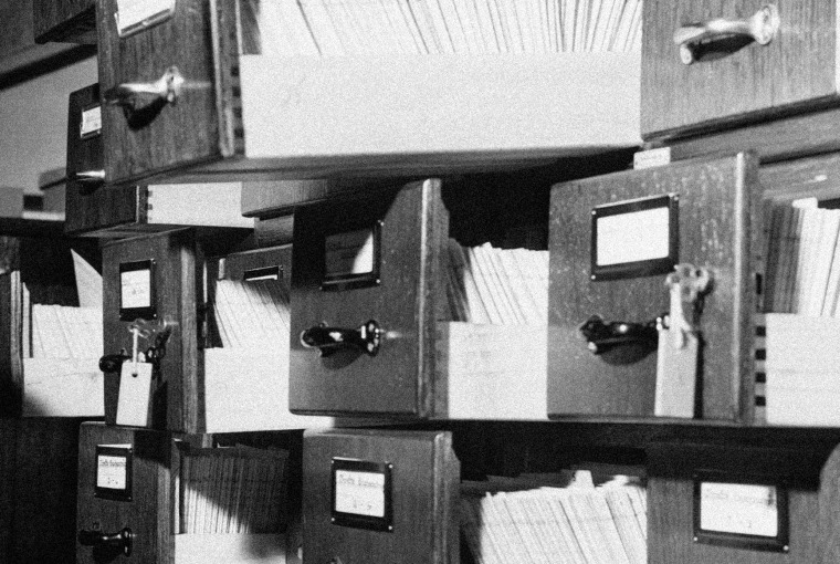 Image of stacks of open filing cabinets with papers.