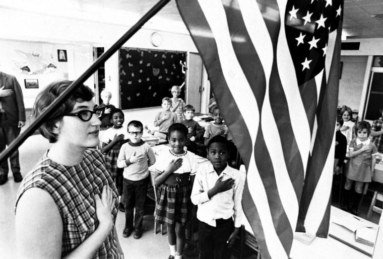 Image: A school teacher and her class recite the pledge of allegiance in Cincinnati, Ohio, c. 1970.