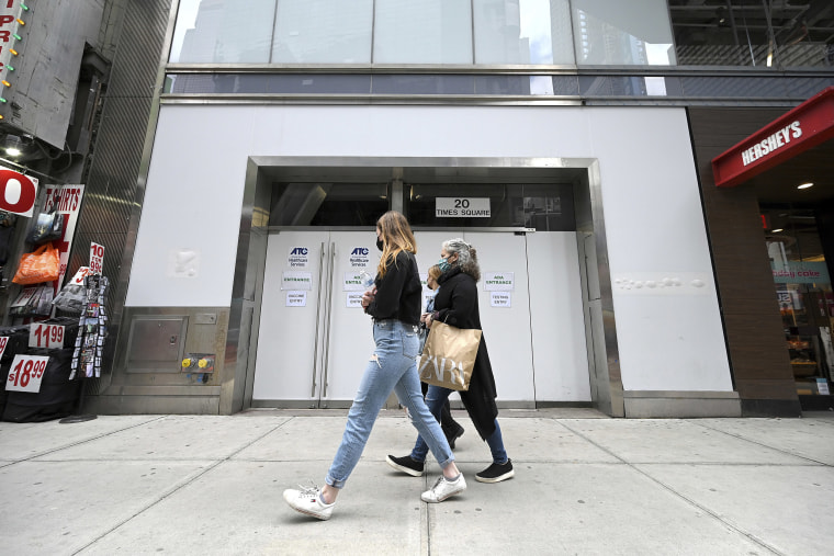 Image: People walk past the newly opened Covid-19 vaccination site in Times Square serving the Broadway theatre film and TV industry workers, New York