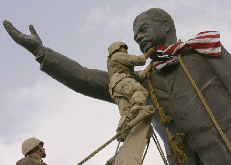 Image: A U.S. marine covers the face of a statue of Saddam Hussein with an American flag before toppling the statue downtown Baghdad