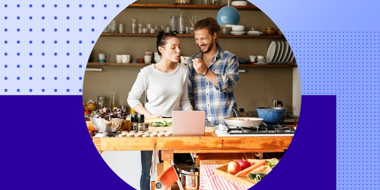 Young couple preparing spaghetti together, using online recipe in kitchen