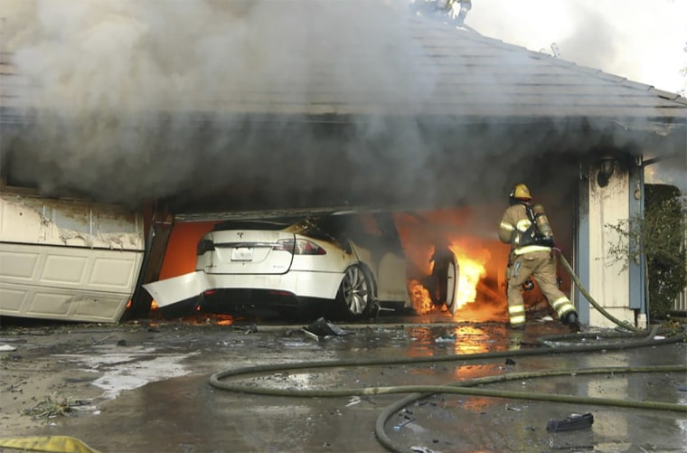 The Orange County Fire Authority battles a fire from a burning Tesla after it crashed into a garage in Lake Forest, Calif., on Aug. 25, 2017. When firefighters removed the SUV from the garage to assess the fire, they identified the fuel source as the SUV's high-voltage battery pack.
