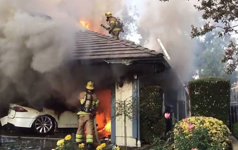 Firefighters battle a blaze sparked by a Tesla in Lake Forest, Calif., on Aug. 25, 2017.