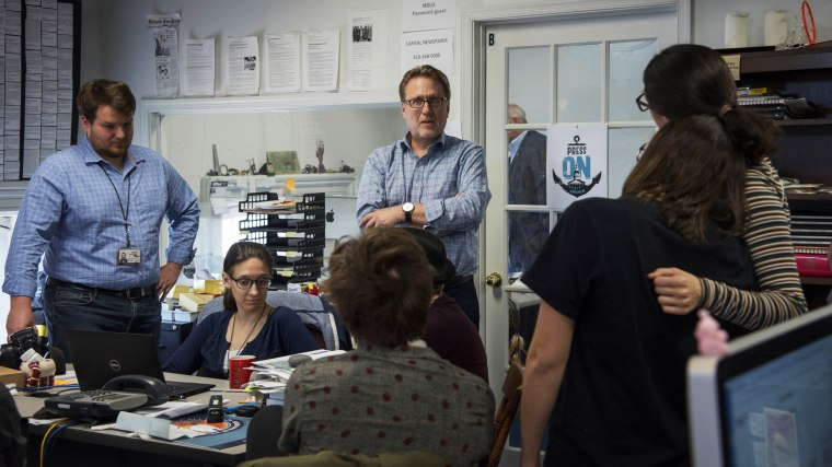 Editor Rick Hutzell, center, gives a speech to his staff at the Capital Gazette in Annapolis, Md., on April 25, 2019.