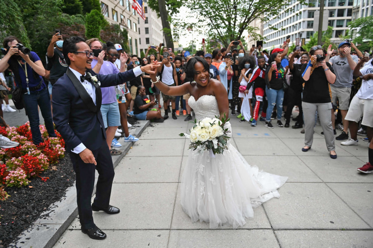 Waizeru Johnson, right, holds the hand of her groom as she walks past people celebrating the Juneteenth holiday at the Black Lives Matter Plaza in Washington, D.C. .