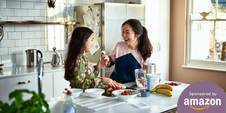 Woman holding yoghurt on spoon towards girl, laughing, threatening to smear food on daughter's face