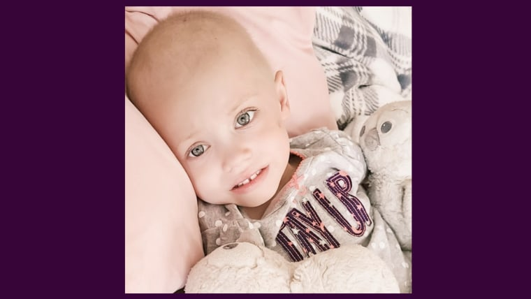 Young girl with green eyes and bald head rests her head on a pink blanket