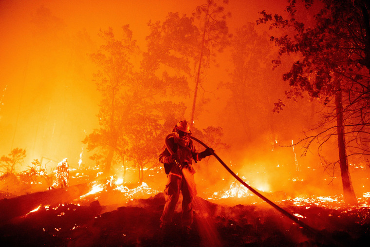 Image: A firefighter douses flames as they push towards homes in California