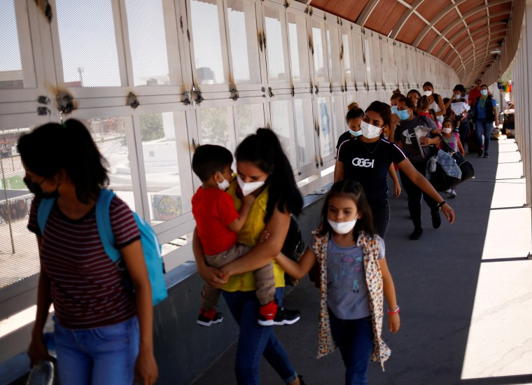 Image: Migrants from Central America, who were previously expelled from the U.S. and sent back to Mexico under Title 42, walk across the Paso del Norte international border bridge in Ciudad Juarez, Mexico