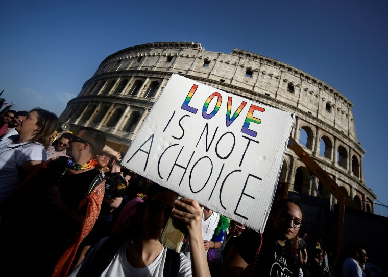Image: Participants walk past the Colosseum monument in the Italian capital Rome during the annual Gay Pride parade.