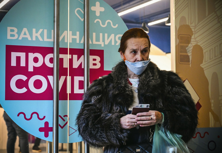 Image: A woman waits to receive an injection of Russia's Sputnik V vaccine against the coronavirus disease at a vaccination point at the GUM department store in Moscow