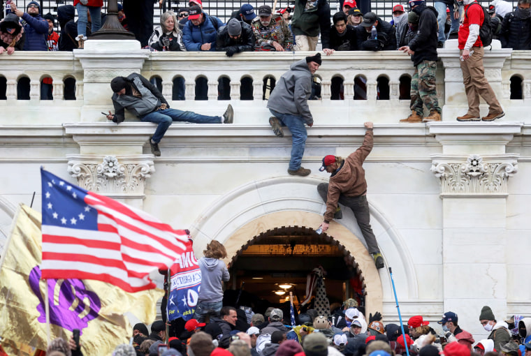 A mob of supporters of President Donald Trump scale a wall as they storm the Capitol on Jan. 6, 2021.