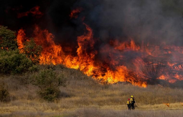 Image: Firefighters battle brush fire burning in the Santa Fe Dam Recreation Area, in Irwindle, California.
