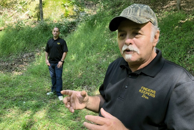 Dennis Parada, right, and his son Kem Parada stand at the site of the FBI's dig for Civil War-era gold in Dents Run, Pa., on Sept. 20, 2018.