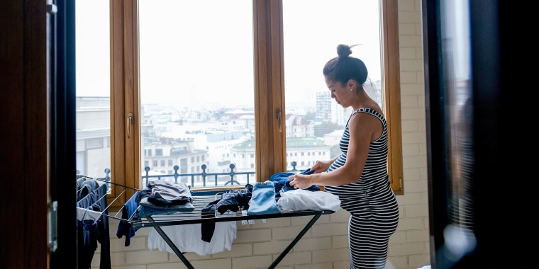 Pregnant woman folds clothing that have been drying on a drying rack. A large window overlooks a city. See the best clothes drying racks for laundry. Shop drying racks for clothes from Amazon, Walmart, Wayfair and more to make drying delicates easier.