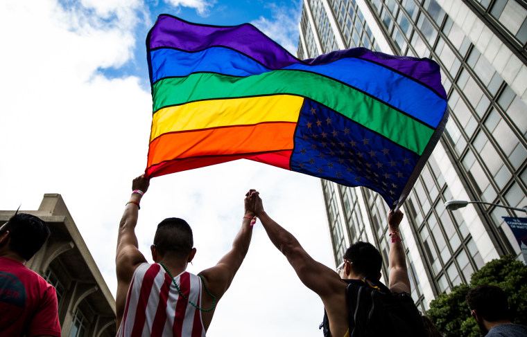 Image: A couple hold up a gay pride flag.