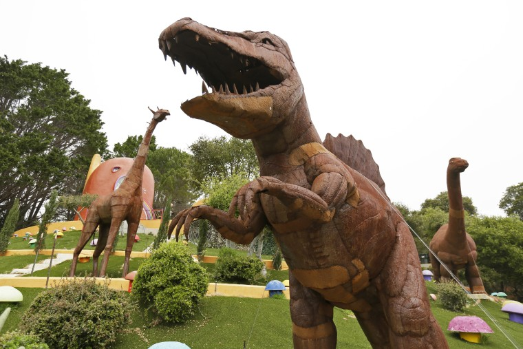 Dinosaurs and other figurines stand in the backyard of the Flintstone House in Hillsborough, Calif., on April 1, 2019.