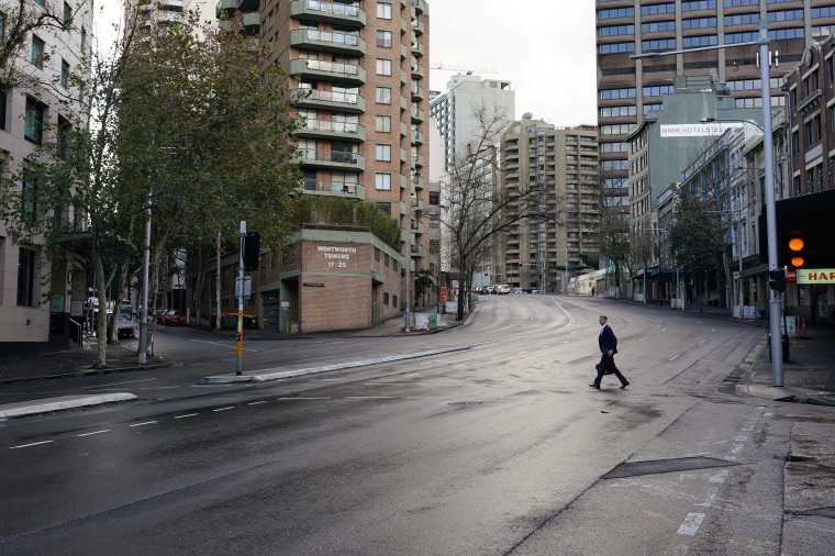 Image: A pedestrian crosses an empty intersection at morning commute hour in the city center during a lockdown to curb the spread of a coCovid-19 outbreak in Sydney, Australia