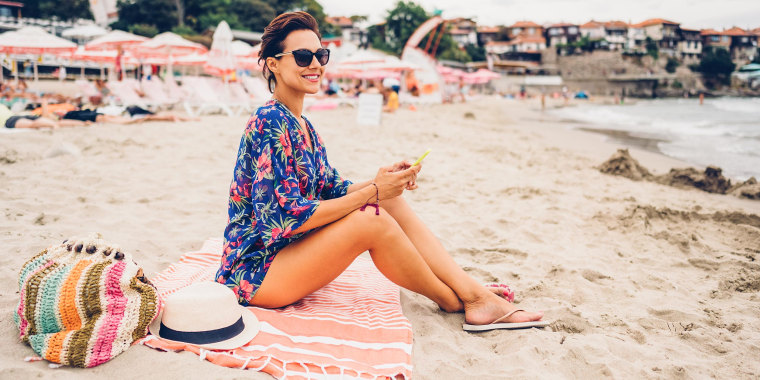 Woman sitting on the beach on a Turkish towel