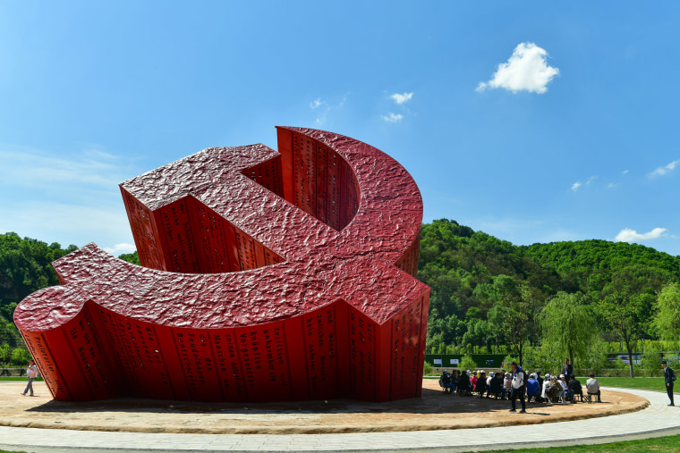 Image: Tourists watch a sculpture featuring the emblem of Communist Party of China at a square of Nanniwan Town on May 17, 2021 in Yan'an, Shaanxi Province of China.