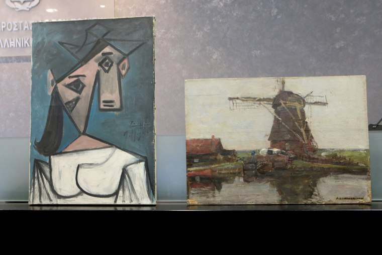 """Image: The stolen \""""Head of a Woman\"""" by Picasso and Piet Mondrian's \""""Stammer Windmill\"""" paintings on display at a press conference, in Athens, Greece"""